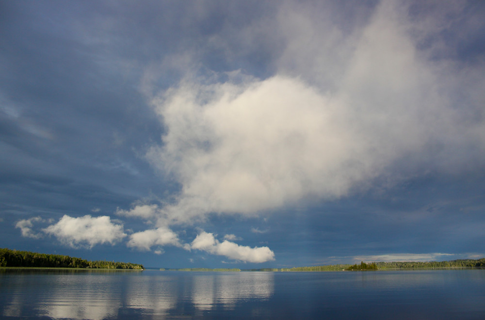 Dark clouds hang over a still Lake Abamasagi