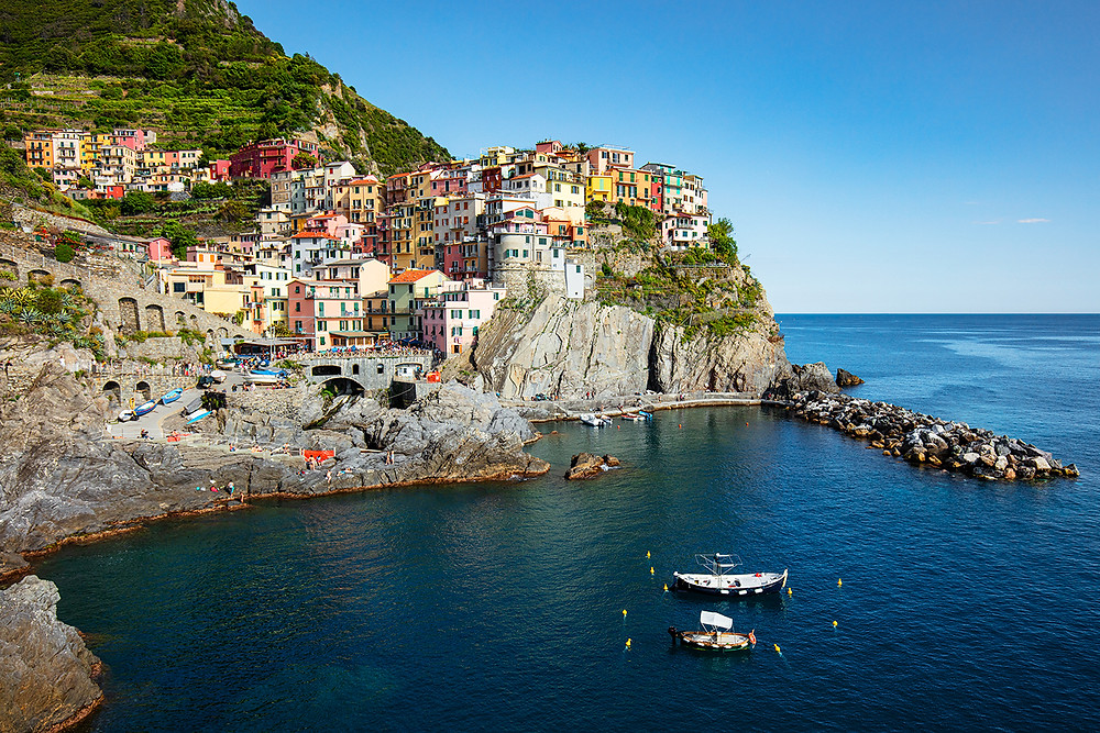The coastal Italian town of Manarola shines bright and colorful in the afternoon sun overlooking the water