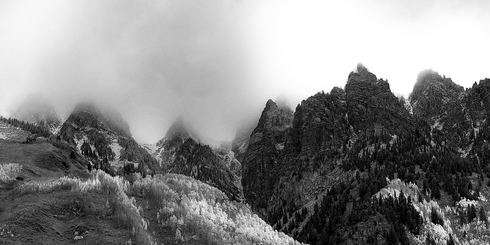 Low clouds diffuse the rising sun over jagged mountain peaks in black and white
