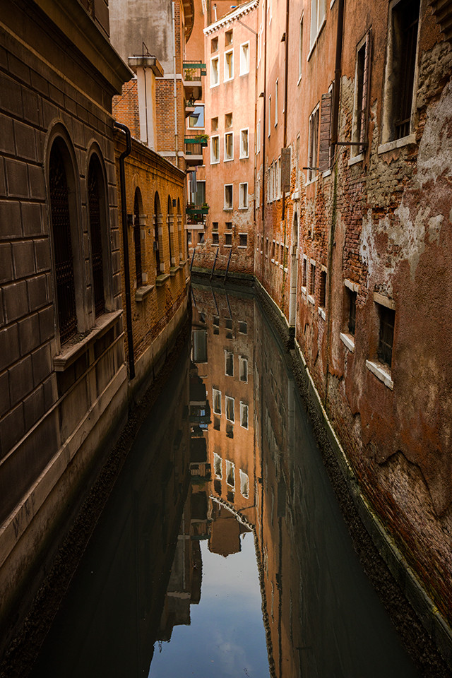 A reflection of a building down a glass like canal in Venice.