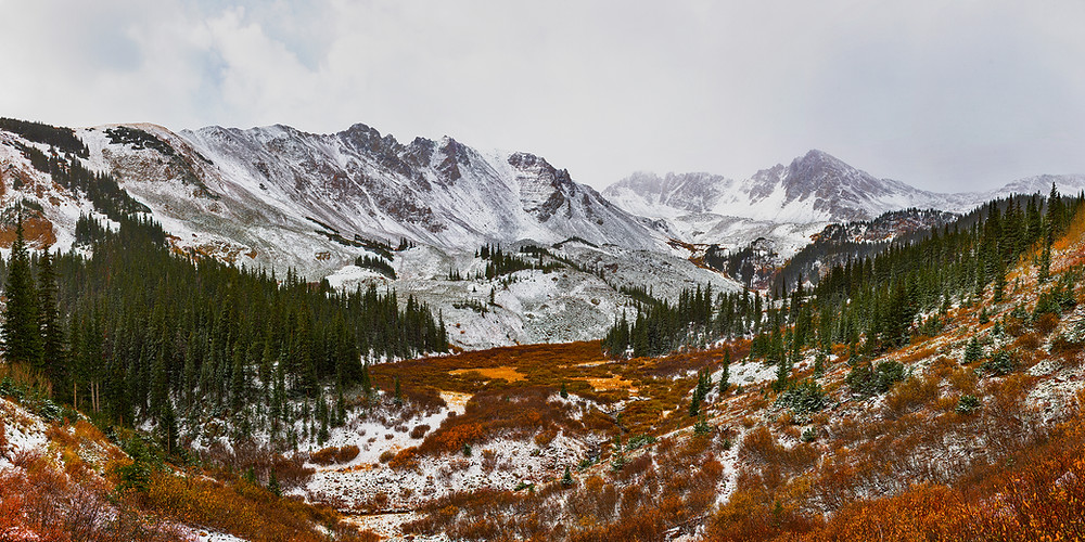 A rocky mountain valley dusted in snow in the peak of autumn