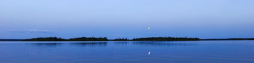 Minimalist photograph of still evening lake in Ontario Canada with the full moon reflecting on the blue water.