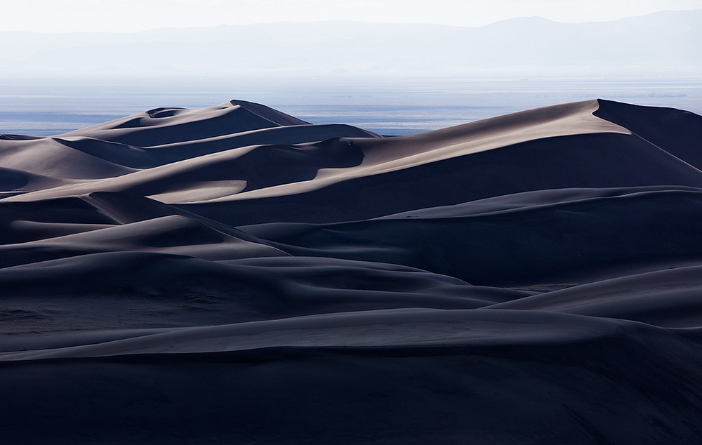 A smooth panorama of the sand dunes in Colorado at dusk.