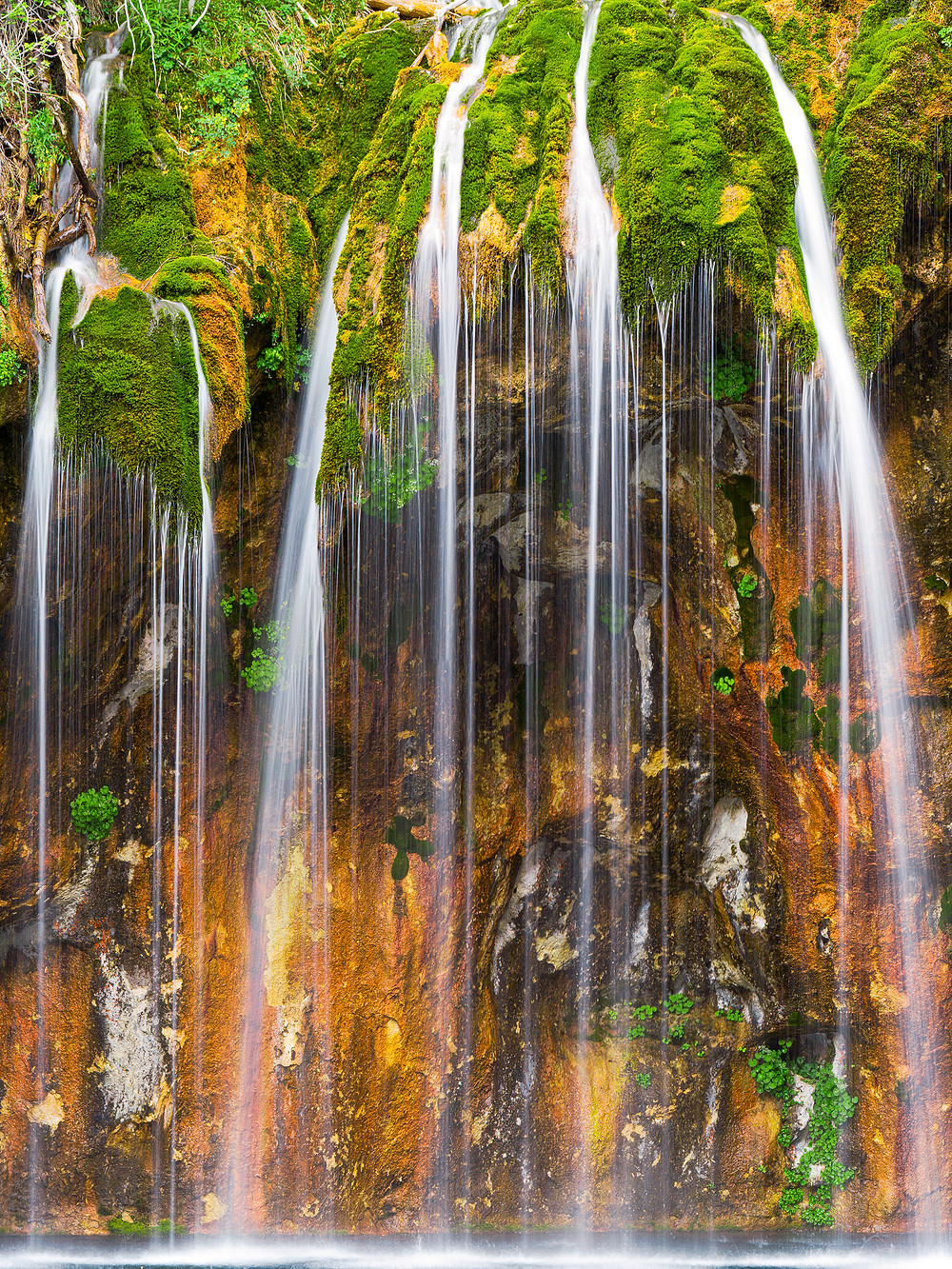 This fine art landscape print of a waterfall in Colorado trickling over a moss covered overhang against a rock wall photographed using a long exposure to blur the water of Hanging Lake.