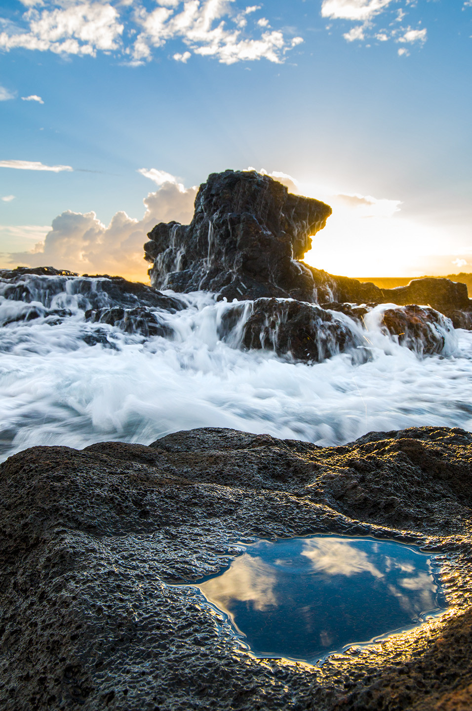 The sun sets behind a rock along the coast of Kauai as the foam of a wave crashes over it.