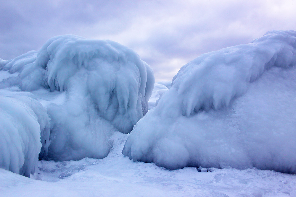 Michigan rocks covered in ice under a grey cloud sky