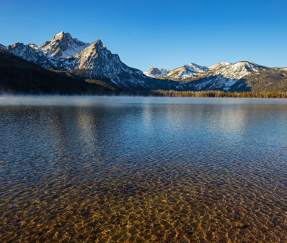 The morning steam lifting off Sawtooth Lake in front of snow covered mountains in Idaho.