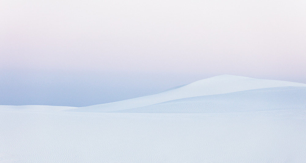 A pastel pink and purple sky over the white dunes of New Mexico