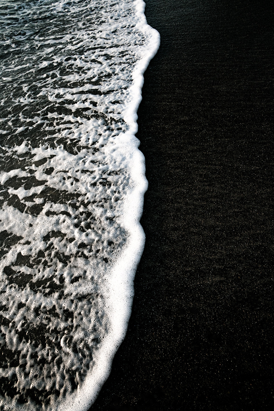 An abstract black and white photo of a wave rolling onto the beach in Costa Rica.
