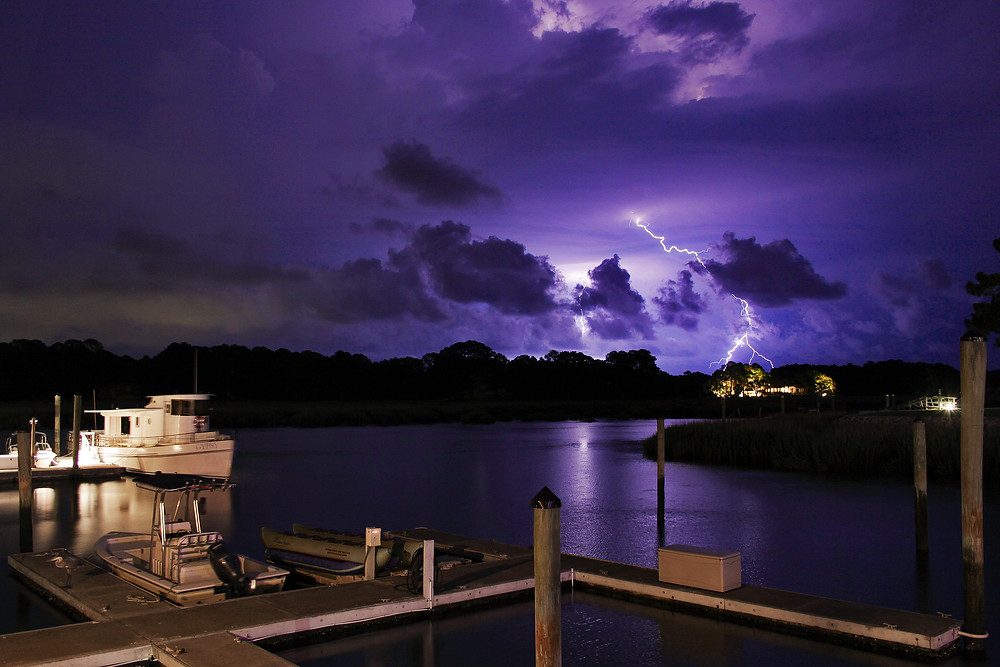 A lightning strike flashes in the purple sky over the water in Hilton Head, South Carolina.