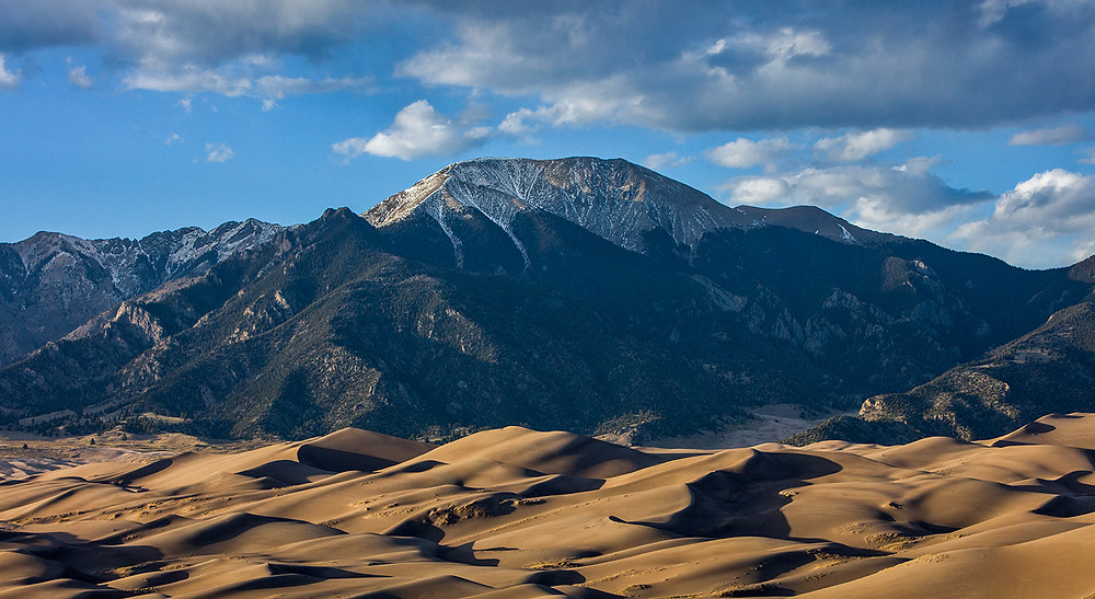 A panorama of Great Sand Dunes National Park in Colorado with the snow capped peaks towering over the dune field.