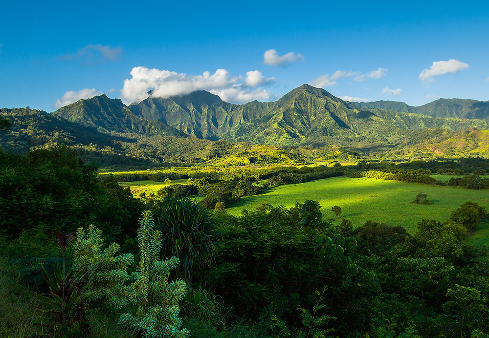 Clouds hang over the mountains on Kauai as the sun begins to soak the landscape