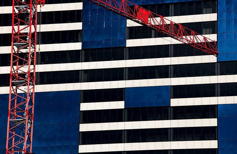 A red crane positioned in front of a black, white, and blue geometric building in Denver, Colorado.