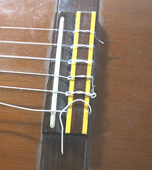 Prendendo a corda no cavalete do violão