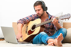 Homem assistindo aula de violão no computador