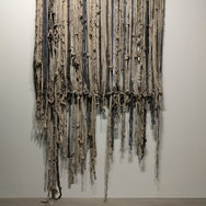 """""""Buried Lines"""" cotton stretched linen bandages and strips of linen either dipped in concrete or navy clay slip, or smeared with graphite dust-stretched and hung on a wooden frame loom. 3'x 3'x 2"""" 2019"""