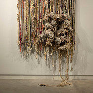 """""""Night Aggregations"""" cotton stretched linen bandages, strips of linen, discarded yard, wool, string, various discarded fibers, and repurposed rope all covered in unfired stoneware-stretched and hung on a wooden frame loom.  48""""x 48""""x 120"""" 2018"""