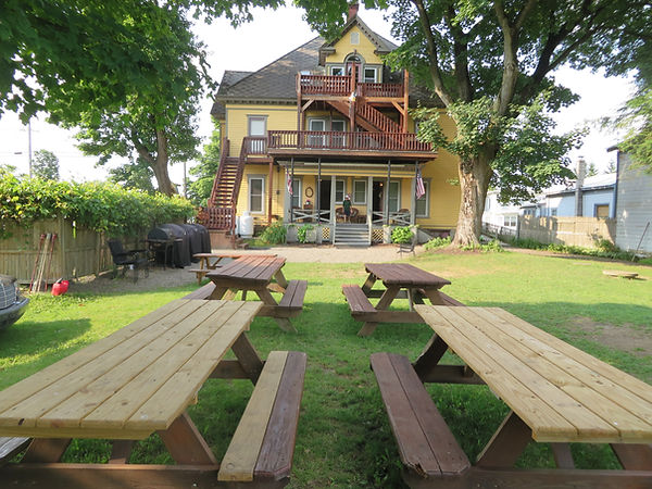 Back of Big yellow victorian house in Milford New York 5 minutes from Cooperstown NY, Owned by Cooperstown Connection and Best Cooperstown Lodging Inc. Home rental in Cooperstown NY sleep 50+ people in 9 connected suite apartments for rent Milford NY
