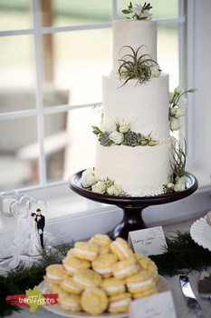 Three tiered white cake decorated with succulents and roses accompanied by lemon whoopie pies.
