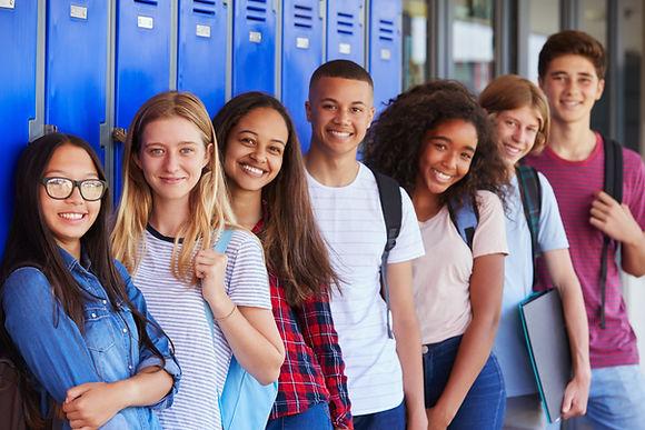 Teenage school kids smiling to camera in school corridor.jpg