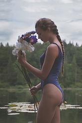 蓮池の前で花を持って立つ水着の女性