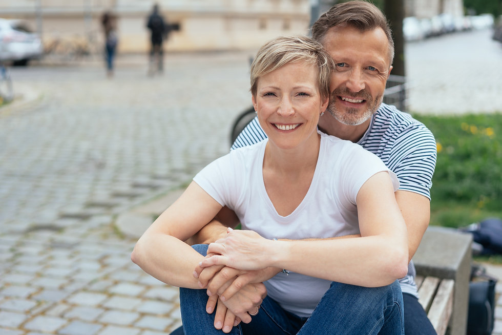 Happy middle-aged couple sitting arm in