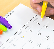 A hand holding a pen, hovering over a paper monthly calendar.
