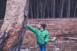 Chłopiec oparty o drzewo