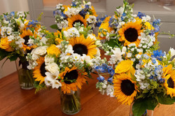 An array of sunflower arrangements are placed on a table before being placed at a reception.