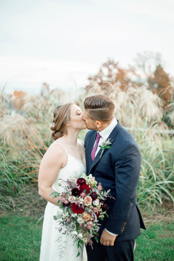 A photo of the newlyweds kissing in front of bushes.