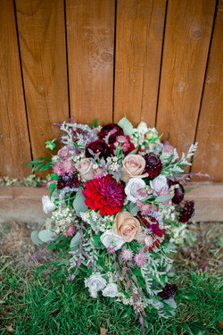 A close-up image of the bridal boquet placed on the ground by the barn.