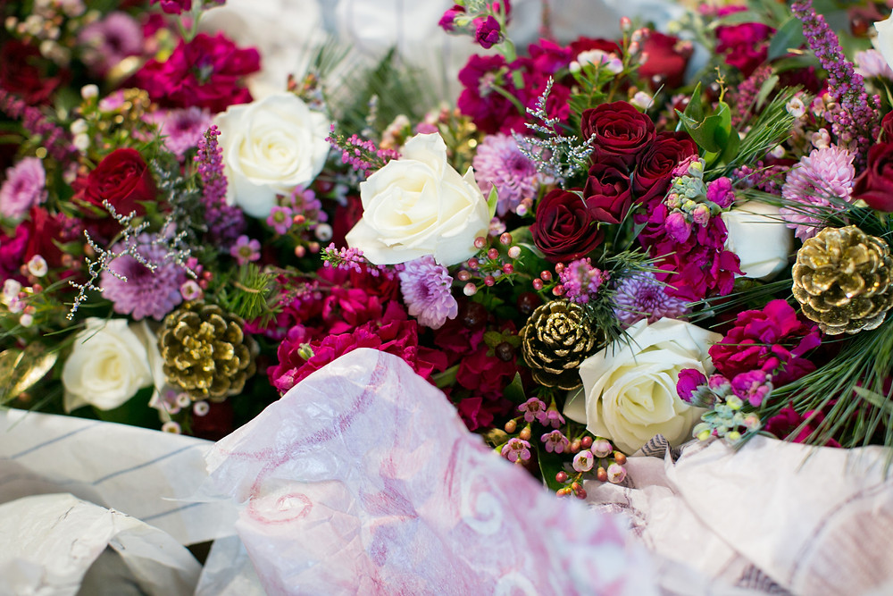 Close-up image of winter wedding bouquet with white & cranberry roses, & golden pinecone decorations.