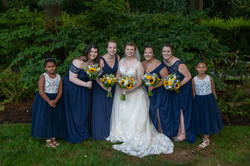 The bride poses with her bridesmaids and junior bridesmaids in front of green bushes.