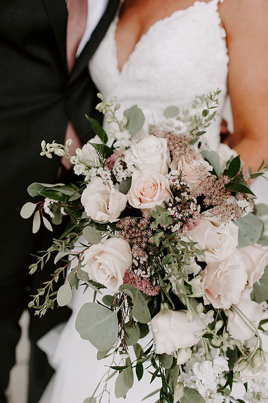 Close up photo of bride holding her bouquet, white & pink roses w/ assorted greenery