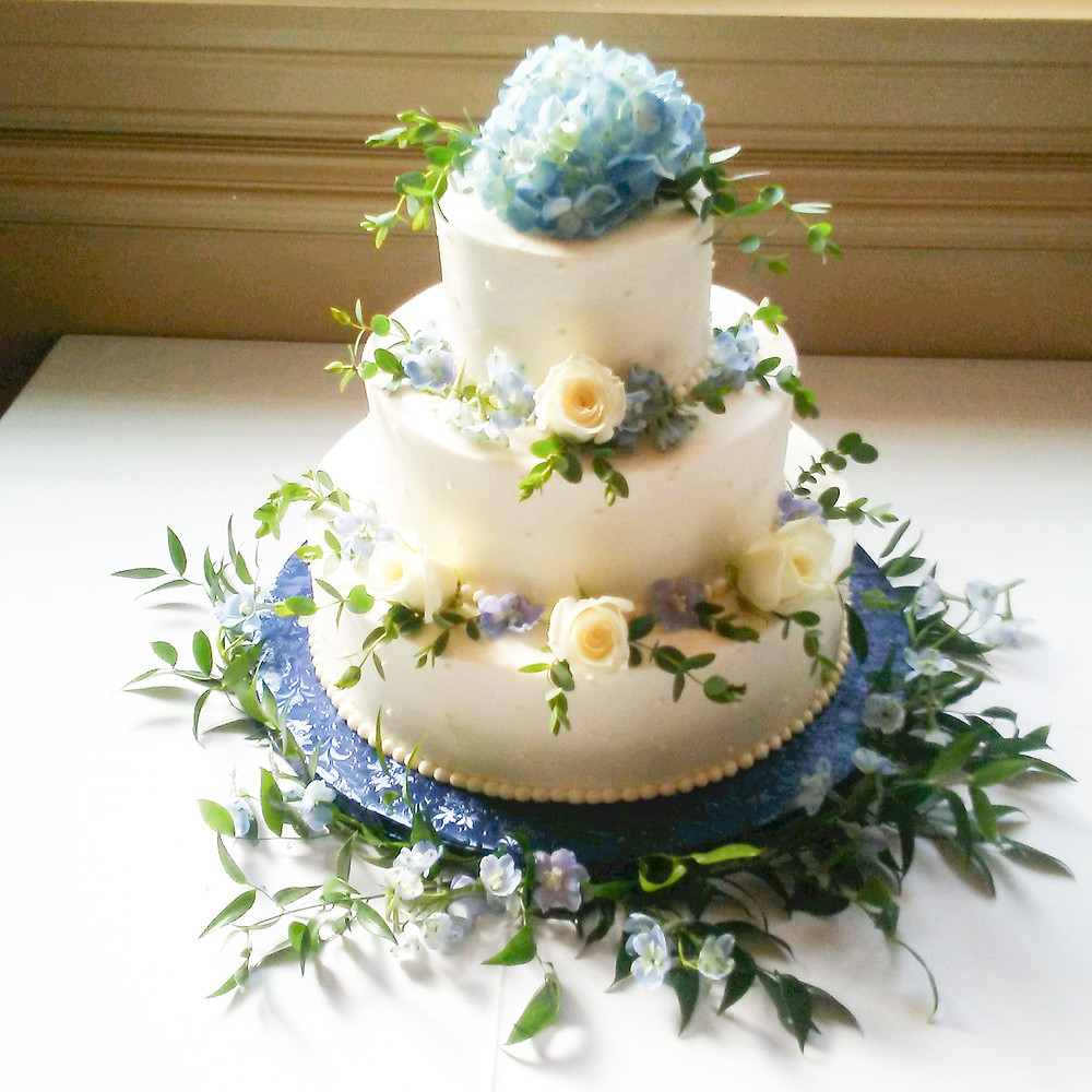Flowers and greenery circling each tier with floral cake topper