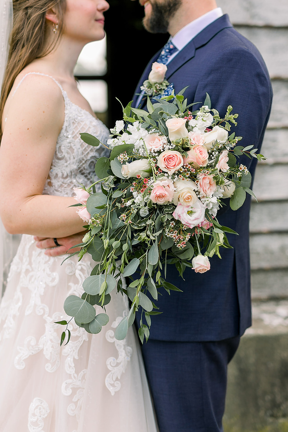 Newlyweds look at each other and pose for a photo. Bridal bouquet w/ peach & white roses, assorted greenery.