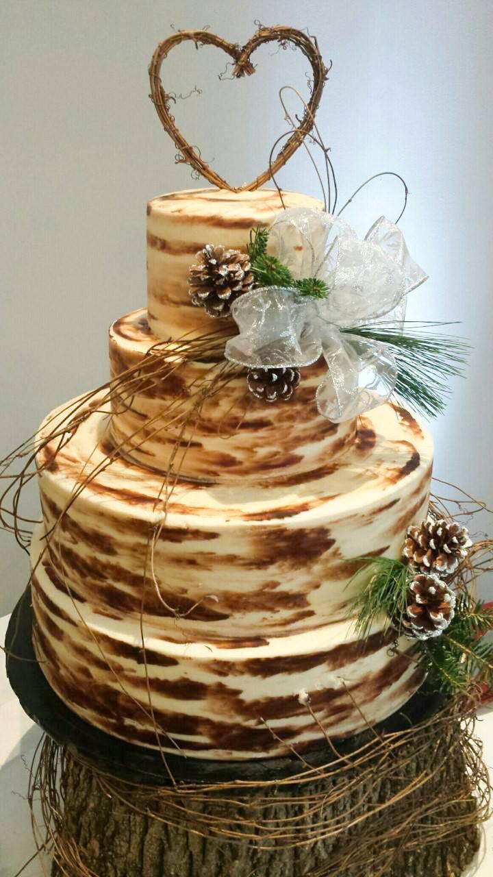 Wedding cake w/ Greenery, pinecones, and ribbon