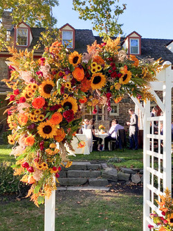 Fall flower arrangement hanging from an arbor at the ceremony.