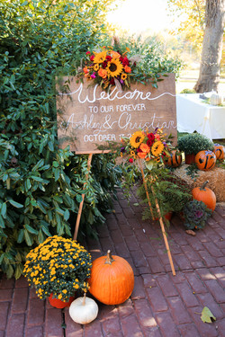 Fall wedding, ceremony welcome sign, surrounded by pumpkins and fall-themed floral arrangements.
