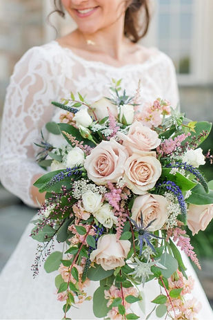 Bride holds her bouquet, pink roses w/ assorted greenery, lace wedding dress shown in the background