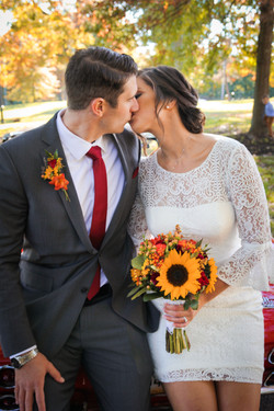 Newlywed couply kisses while posing with their sunflower & fall themed arrangements.