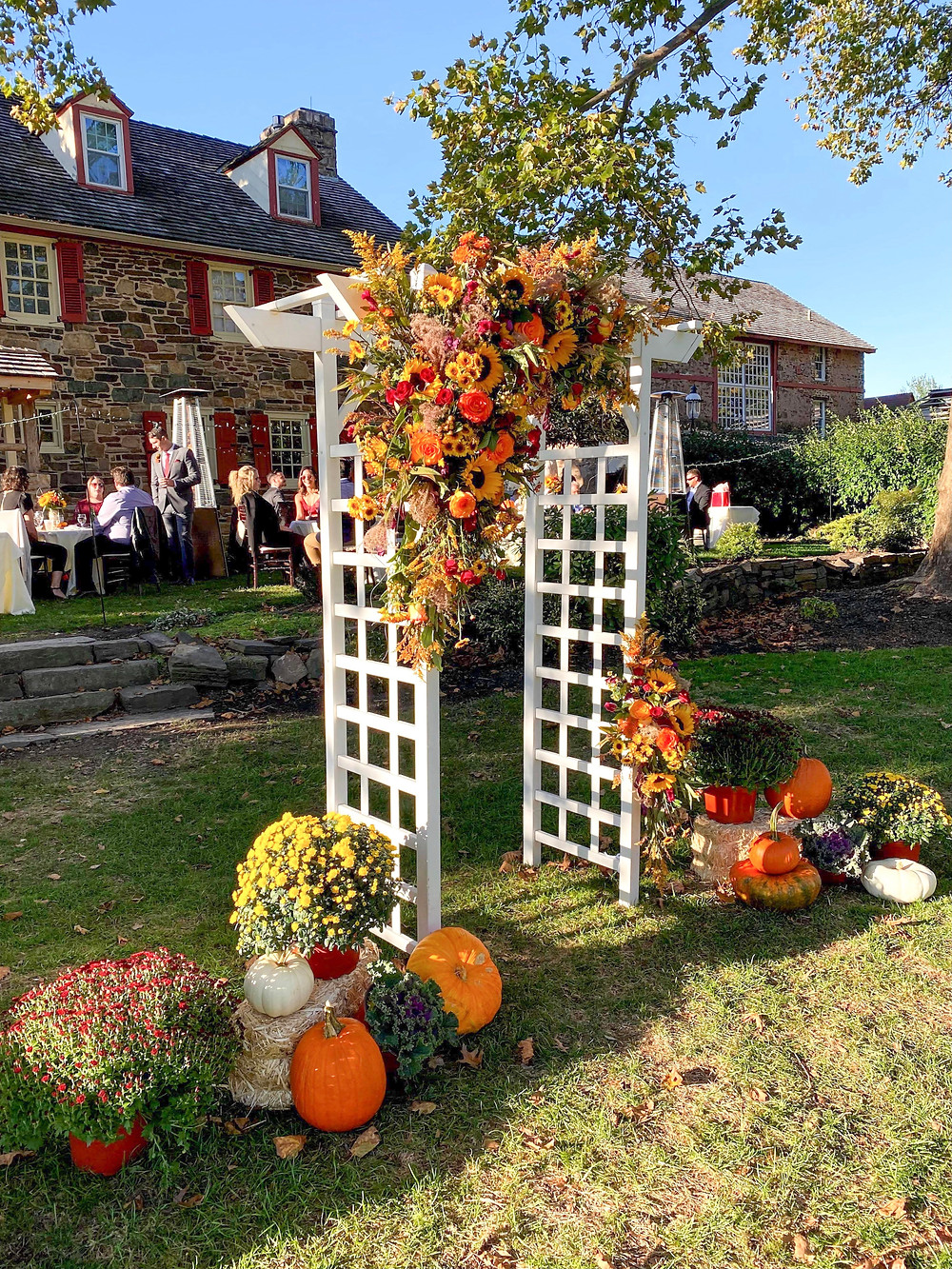 A fall wedding ceremony arbor with hanging sunflower arrangement surrounded by fall flowers and pumpkins at the base.