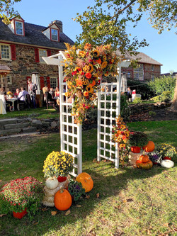 Fall flower arrangement hanging from an arbor at the ceremony, surrounded by pumpkins at the base.