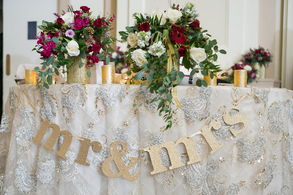 """The sweetheart table decorated with a gold """"mr & mrs."""" sign, and floral arrangments w/ white & cranberry flowers."""
