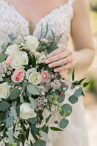 Close up photo of bride holding bouquet, pink, purple, and white flowers, brides hand & ring shown as well