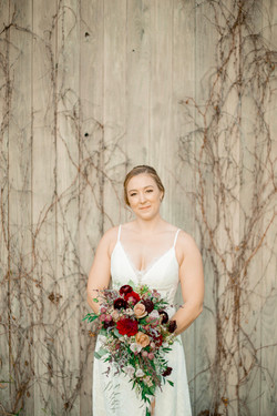 Bride poses in front of grey barn door with her fall-themed bouquet.