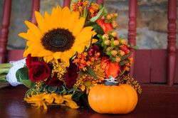 Fall bouquet with sunflower next to pumpkin with the set of rings posed on top.