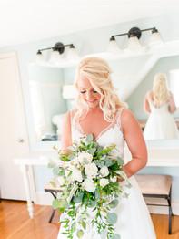 Bride smiling at bouquet - Barn on Bridge - Andrea Krout Photography