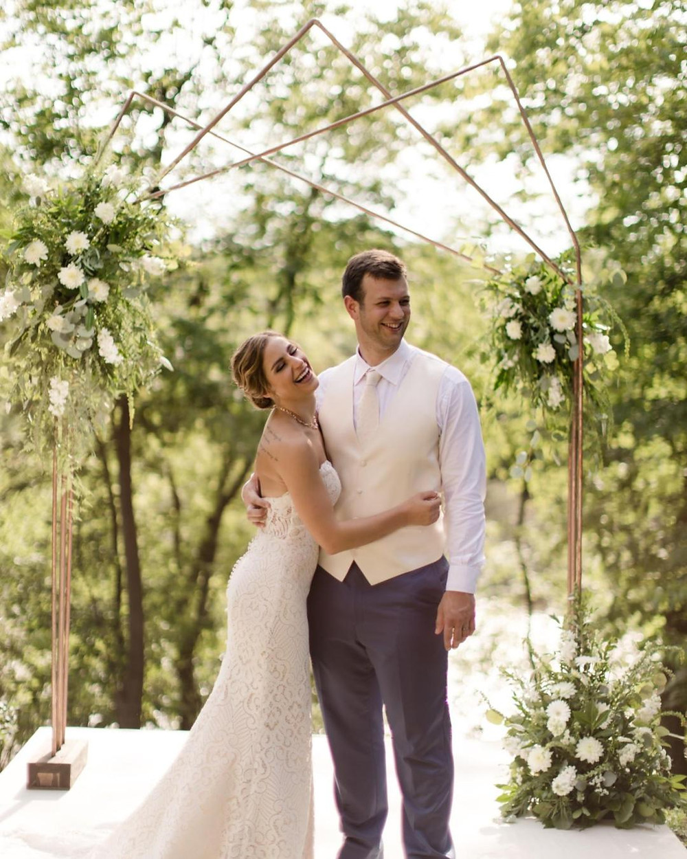 A couple laughs together under their ceremony arbor. White flowers w/ greenery.