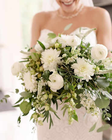 Close up image of bride holding her bouquet, background blurred w/ bouquet clear, large white flowers w/ flowing greenery